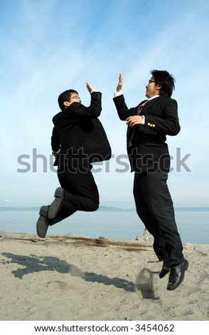 Two businessmen jumping happily on the beach - stock photo