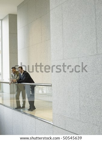 Two businessmen leaning on railing in office building