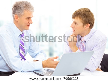 Two businessmen looking at a laptop in office - stock photo