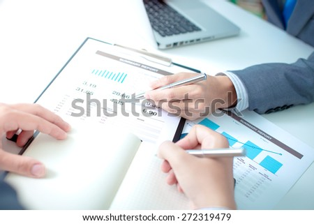 Two businessmen looking at report and having a discussion in office. - stock photo