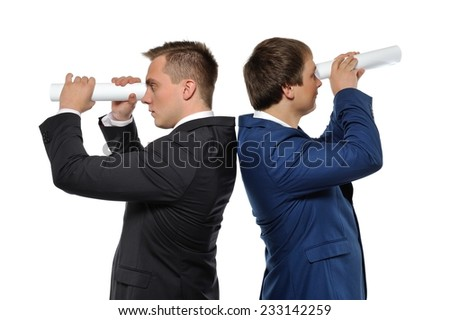 Two businessmen looking through a rolled paper. Business vision, or headhunters concept. - stock photo