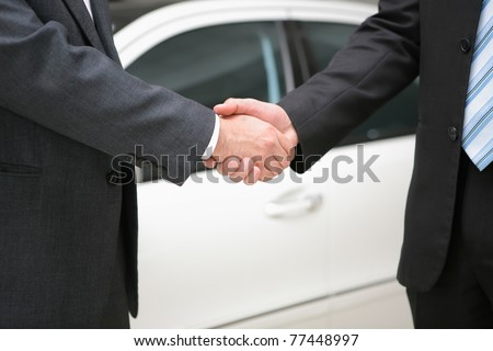 two businessmen making handshake with a luxury car at the back - stock photo