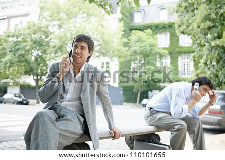 Two businessmen making phone calls on their cells while sitting on a bench in the financial district of the city. - stock photo