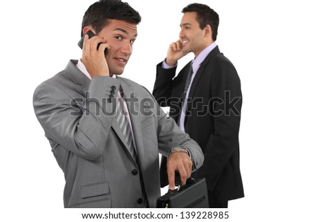 Two businessmen making telephone calls