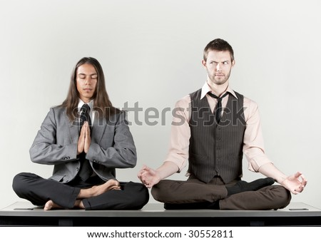Two businessmen meditating on their office desk