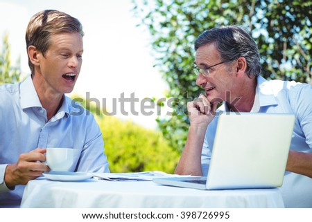 Two businessmen meeting in a restaurant using laptop in the garden - stock photo