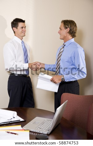 Two businessmen meeting in office shaking hands - stock photo