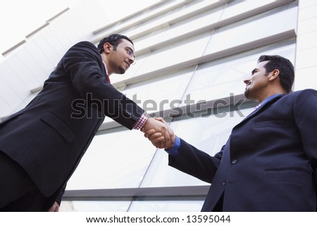Two businessmen meeting outside modern office building - stock photo