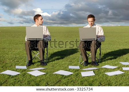 Two businessmen on Laptops in a field. - stock photo