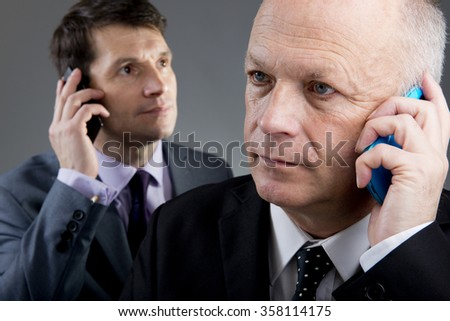 Two Businessmen On Their Mobile Phones - stock photo