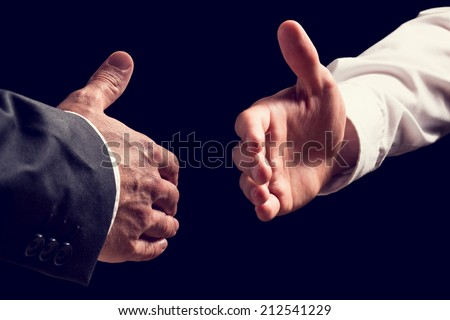 Two businessmen, one in a shirt and one in a suit, about to shake hands as they reach out towards one another conceptual of a partnership, agreement, deal, greeting or congratulations. - stock photo