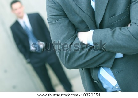 two businessmen one standing in front of the other with the first folding his arms and the second with hands in pockets - stock photo