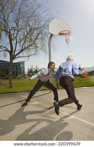 Two businessmen playing basketball - stock photo
