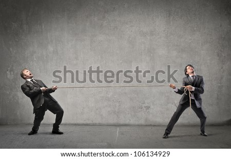 Two businessmen playing tug of war - stock photo