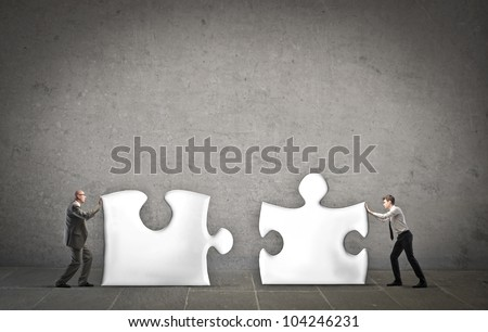 Two businessmen putting together two puzzle pieces