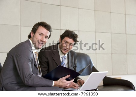 Two businessmen seated with a laptop