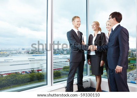 Two businessmen shake hands next to business women - stock photo