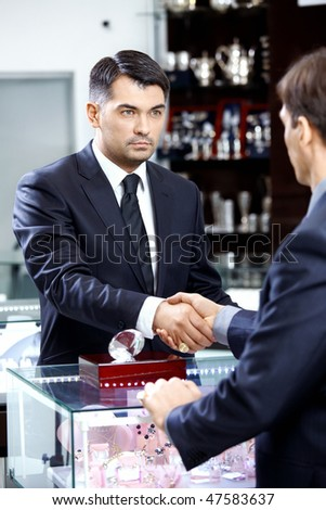 Two businessmen shake hands on a forward background