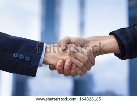 Two businessmen shaking hand with office buildings in background - stock photo