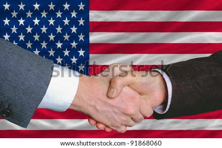 two businessmen shaking hands after good business investment  agreement in america, in front of flag - stock photo