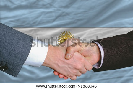 two businessmen shaking hands after good business investment  agreement in argentina, in front of flag - stock photo