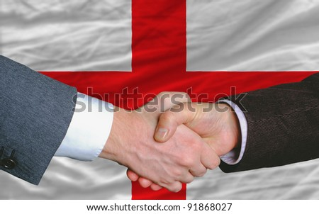 two businessmen shaking hands after good business investment  agreement in england, in front of flag - stock photo