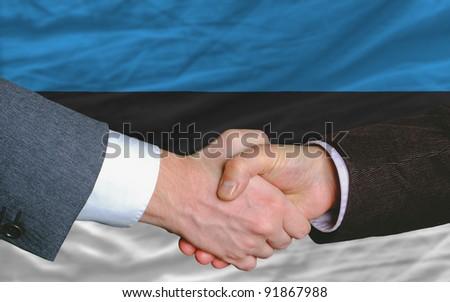 two businessmen shaking hands after good business investment  agreement in estonia, in front of flag - stock photo