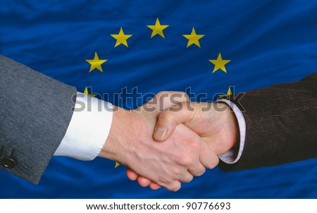 two businessmen shaking hands after good business investment  agreement in europe, in front of flag - stock photo