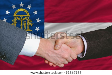 two businessmen shaking hands after good business investment  agreement in georgia, in front of flag - stock photo