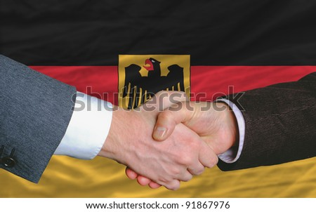 two businessmen shaking hands after good business investment  agreement in germany, in front of flag - stock photo