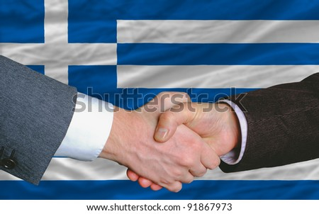 two businessmen shaking hands after good business investment  agreement in greece, in front of flag - stock photo