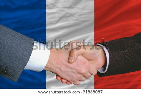 two businessmen shaking hands after good business investment  agreement in iceland, in front of flag - stock photo