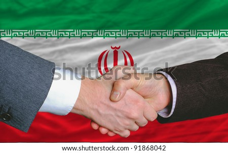 two businessmen shaking hands after good business investment  agreement in iran, in front of flag - stock photo
