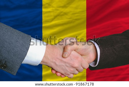 two businessmen shaking hands after good business investment  agreement in romania, in front of flag - stock photo