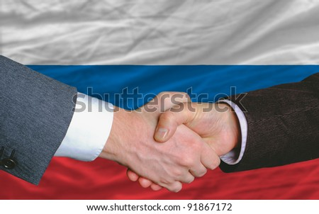 two businessmen shaking hands after good business investment  agreement in russia, in front of flag - stock photo