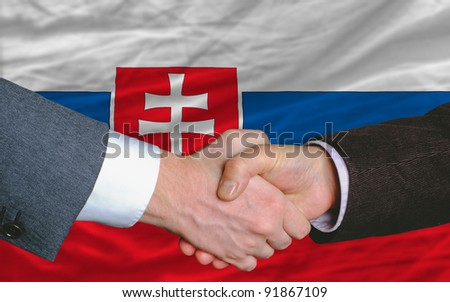 two businessmen shaking hands after good business investment  agreement in slovakia, in front of flag - stock photo