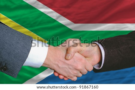 two businessmen shaking hands after good business investment  agreement in south africa, in front of flag - stock photo