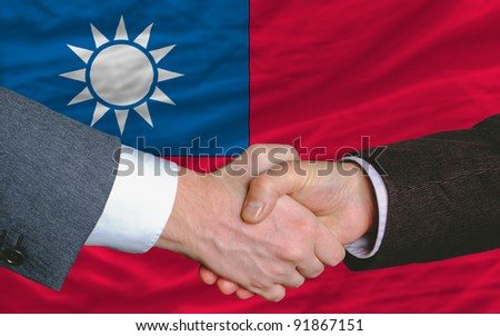 two businessmen shaking hands after good business investment  agreement in taiwan, in front of flag - stock photo