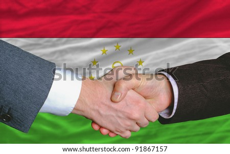 two businessmen shaking hands after good business investment  agreement in tajikistan, in front of flag - stock photo
