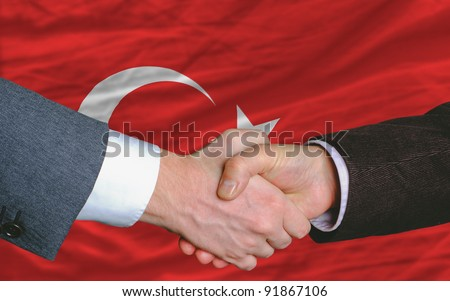 two businessmen shaking hands after good business investment  agreement in turkey, in front of flag - stock photo