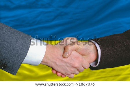 two businessmen shaking hands after good business investment  agreement in ukraine, in front of flag - stock photo