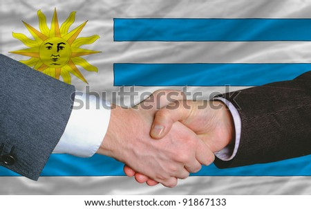 two businessmen shaking hands after good business investment  agreement in uruguay, in front of flag - stock photo