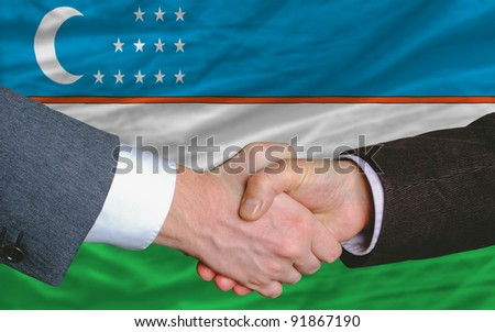 two businessmen shaking hands after good business investment  agreement in uzbekistan, in front of flag - stock photo
