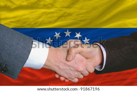 two businessmen shaking hands after good business investment  agreement in venezuela, in front of flag - stock photo