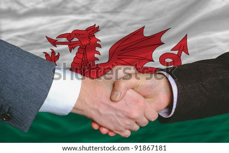 two businessmen shaking hands after good business investment  agreement in wales, in front of flag - stock photo