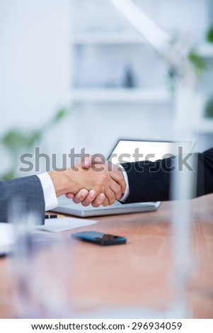 Two businessmen shaking hands and working at the office - stock photo