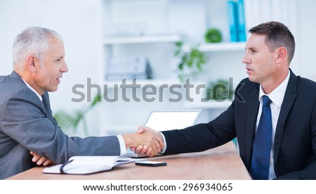 Two businessmen shaking hands and working at the office