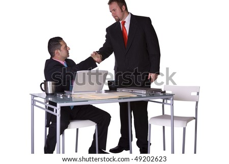 Two Businessmen Shaking Hands at the Desk in an Office