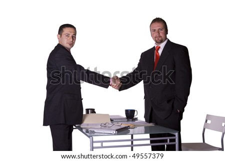 Two Businessmen Shaking Hands at the Desk in an Office - stock photo