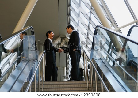 Two businessmen shaking hands at the top of a stairway - stock photo